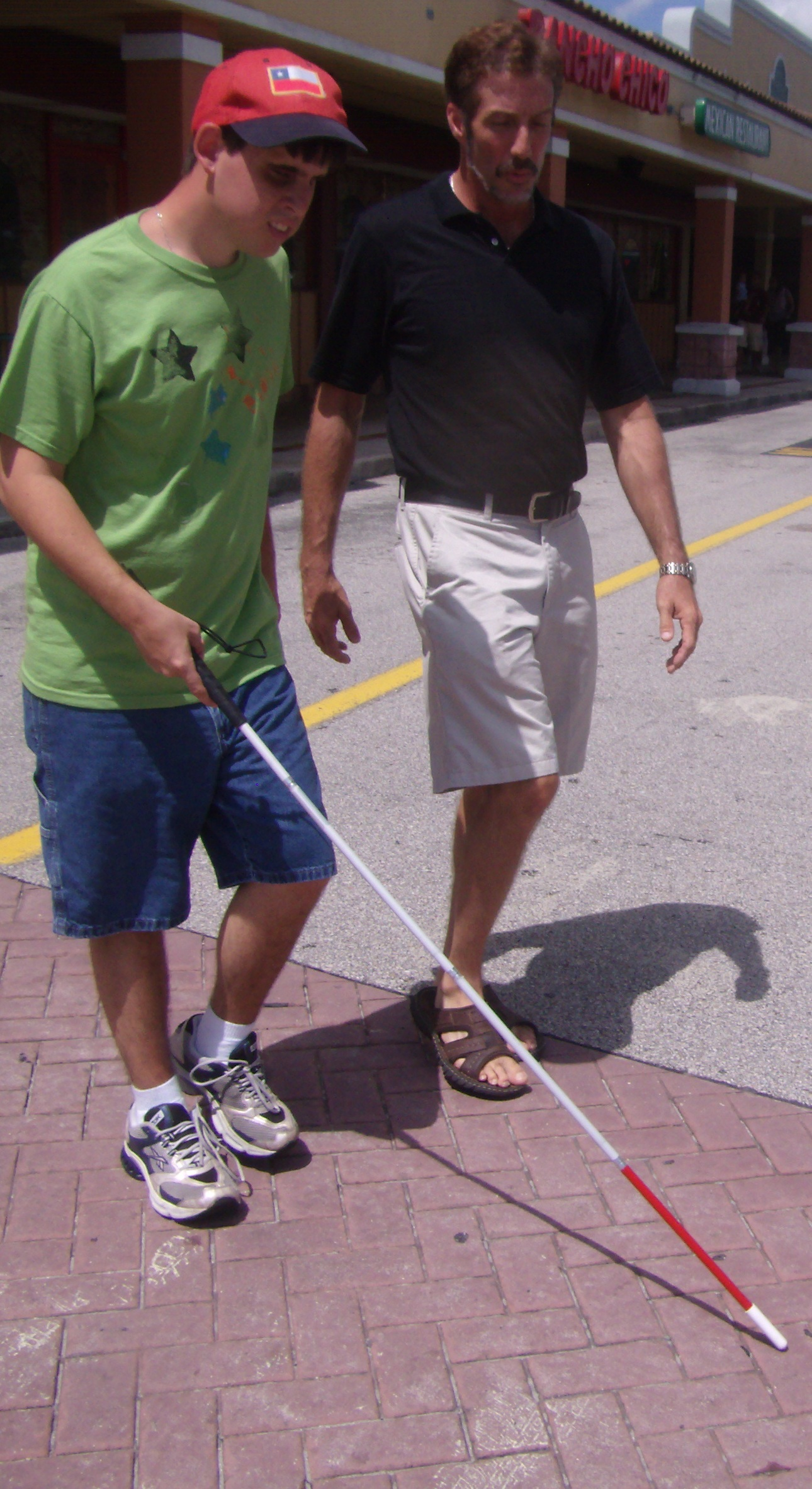 Curt Seeley teaching street crossing techniques to a participant using a white cane