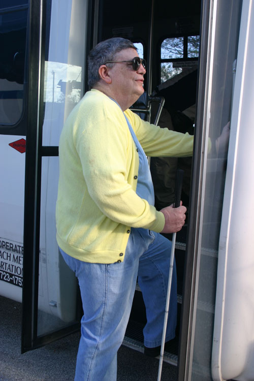 Bobby getting onto a bus using his White Cane
