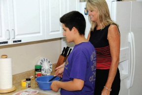 Mary Allen, Director of Vision Services, with Omar Alvarado working in the kitchen