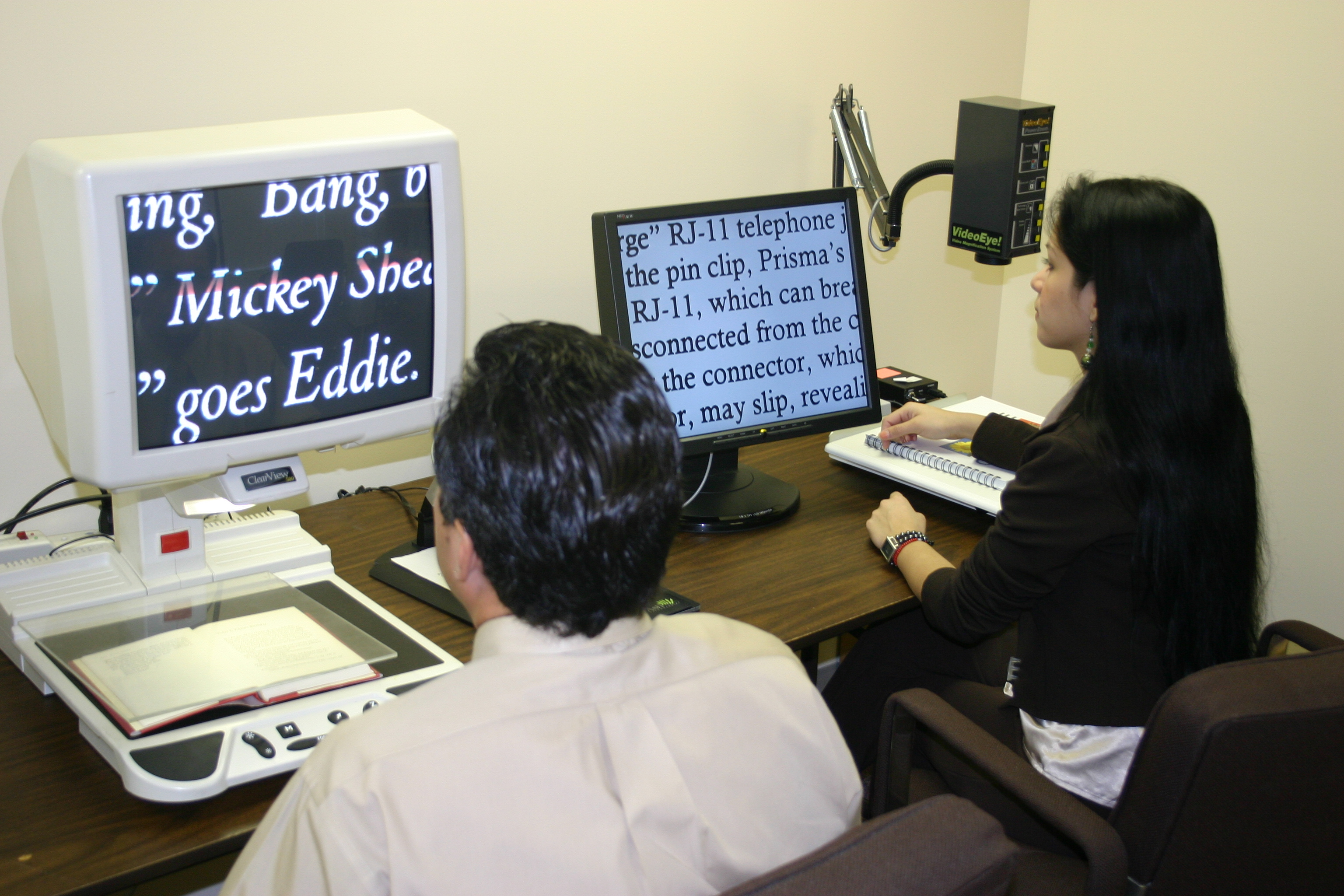 Picture of two people using Closed Circuit Televisions in our Reading Room.