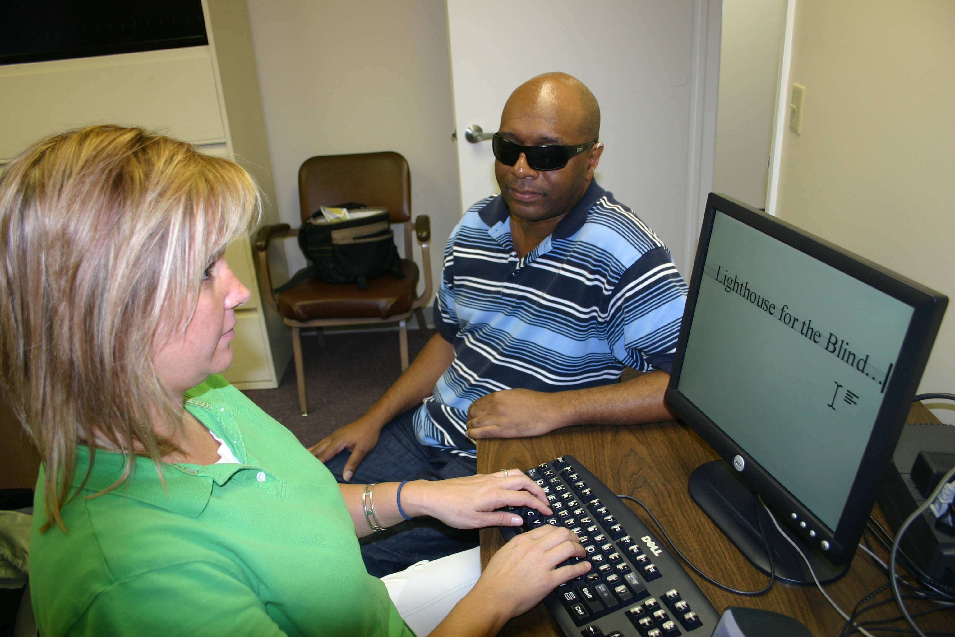 Picture of a Lighthouse technology instructor teaching a woman how to use magnification software.