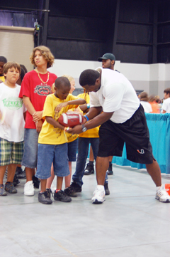 Bennie Blades, former UM and NFL player, teaching Kids Fitness Festival participants the basics of football.